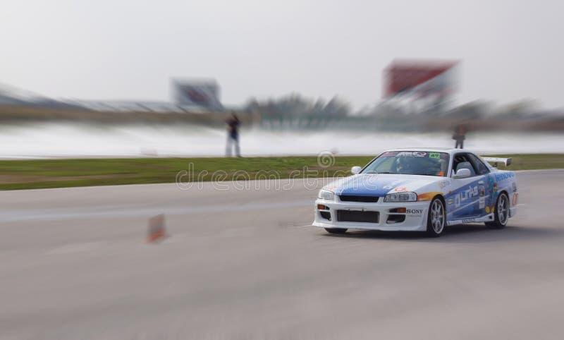 Den Racihg bilen driver mot suddig bakgrund royaltyfria foton