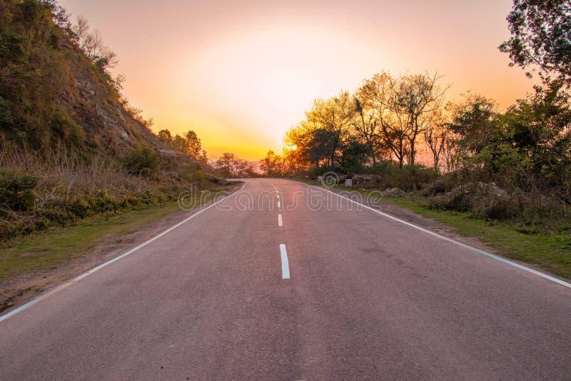 Den raka vägen under solnedgång, motorväg, fastar royaltyfria bilder