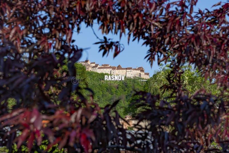 Den Rasnov fästningen från det Brasov länet, Rumänien, sitter på den högsta kullen, som dominerar Rasnov den medeltida byn som be arkivbilder