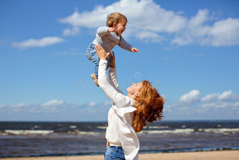 Den Redheaded mamman i jeans och en vit tröja kastar upp hans barn s arkivbild