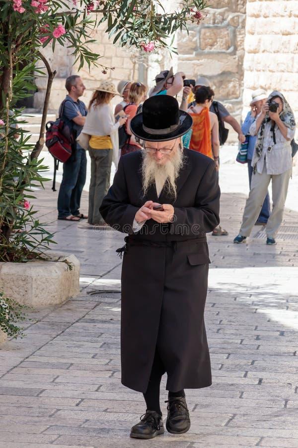 Den religiösa juden promenerar gatan och ser hans mobiltelefon i den gamla staden av Jerusalem, Israel royaltyfri foto