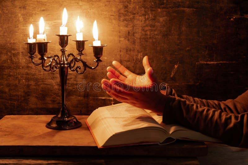 Den religiösa kvinnlign korsade händer i bön med bibeln och stearinljuset royaltyfria bilder