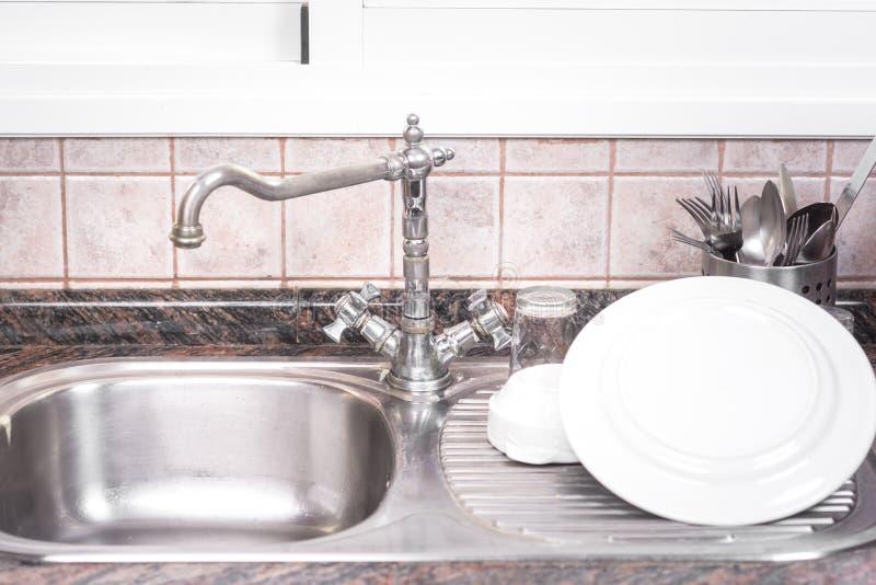 Den rena disken torkar, på lantlig kökmetallvask royaltyfria bilder