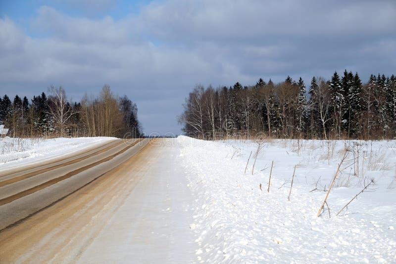 Den renade tomma förorts- sand-beströdde vägen till och med en snowfield och en skog under blå himmel med vit fördunklar på frost arkivfoton