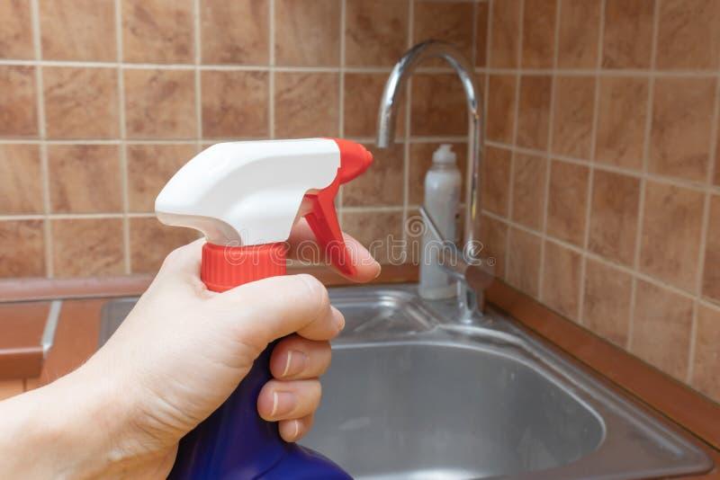 Den rengörande diskhon och vattenkranen med anti-limescalesprej, stänger sig upp sikt av sprejflaskan i hand arkivbild
