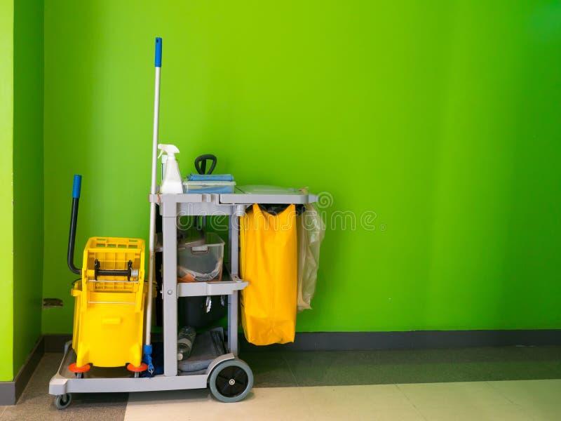 Den rengörande hjälpmedelvagnen väntar på lokalvård Ösregna och uppsättningen av lokalvårdutrustning i kontoret dörrvaktservice s royaltyfri foto