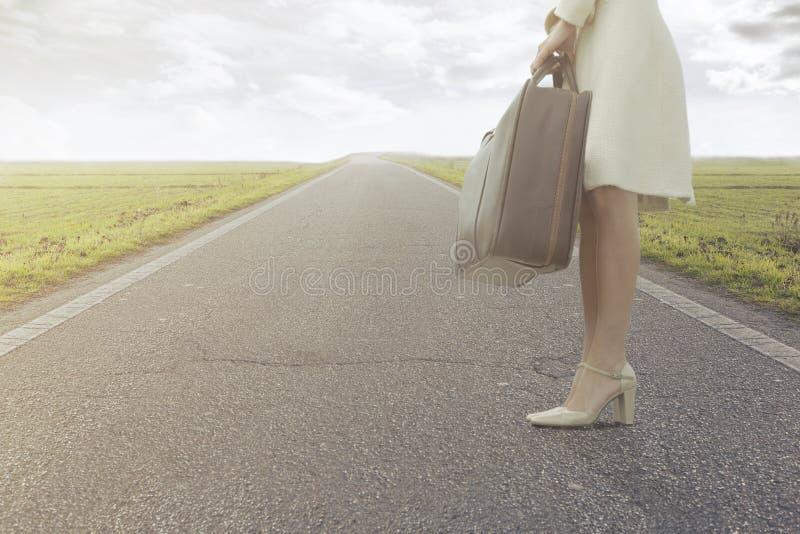Den resande kvinnan väntar med hennes resväska för att lämna för en ny resa royaltyfria bilder
