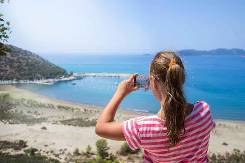 Den resande tonårs- flickan tar en fotobergsikt, loppbegrepp royaltyfria bilder