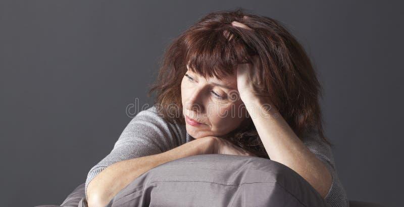 Den resignerade höga kvinnan som är sjuk av att ha klimakterium, slösar royaltyfria bilder