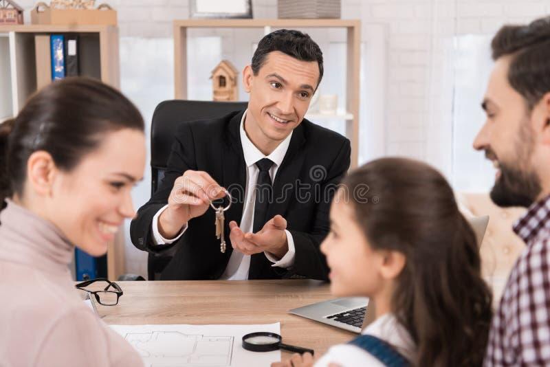 Den respektabla fastighetsmäklaren ger tangenter till det nya hemmet för ung lycklig familj på kontoret royaltyfri foto