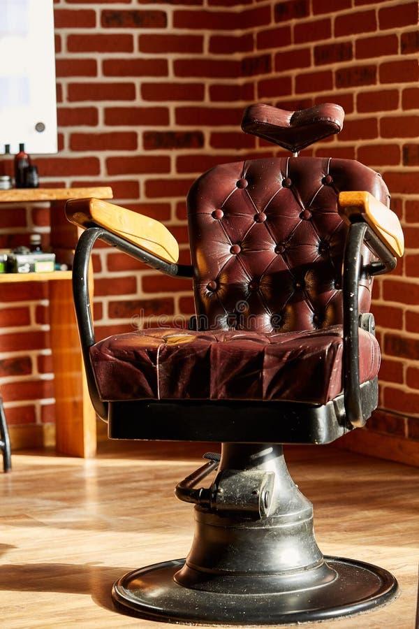 Den Retro barberaren för läderstol shoppar i tappningstil Frisersalongtema arkivfoton
