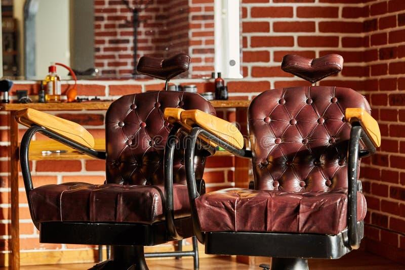 Den Retro barberaren för läderstol shoppar i tappningstil Frisersalongtema arkivfoto