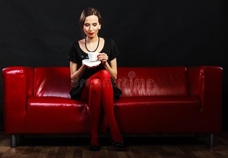 Den Retro kvinnan rymmer sammanträde för tekopp på soffan royaltyfria foton