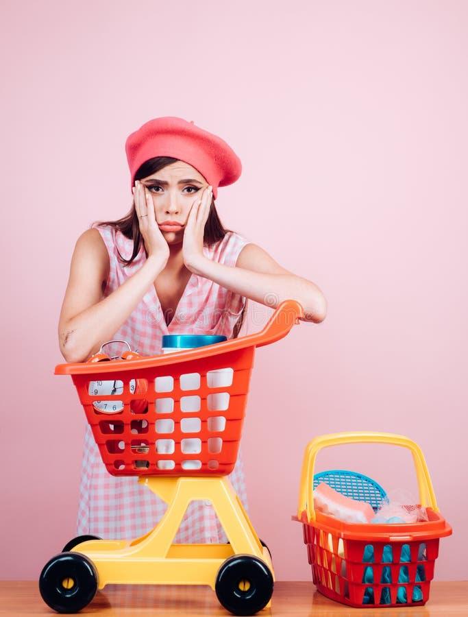 Den Retro parisian kvinnan går att shoppa med den fulla vagnen tappninghemmafrukvinna som är klar att betala i supermarket card g royaltyfria foton