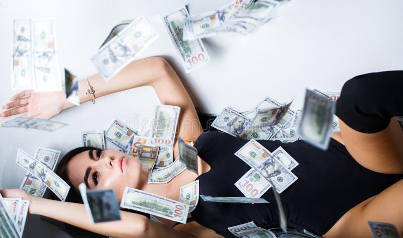 Den rika sexiga kvinnan ligger på pengar Valuta kvinnor som segrar Sexiga kvinnlig- och dollarräkningar Sexig kvinna som ligger i arkivfoto