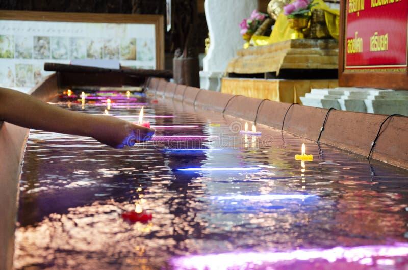 Den rituella be färgrika stearinljuset som svävar på vatten för, ber att vila Buddhabild på Wat Phra Non Chakkrasi Worawihan i Si arkivbild