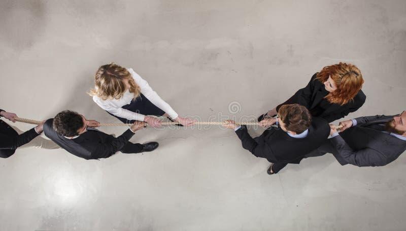 Den rivaliserande den affärsmannen och kvinnan konkurrerar för kommandot, genom att dra repet royaltyfri bild