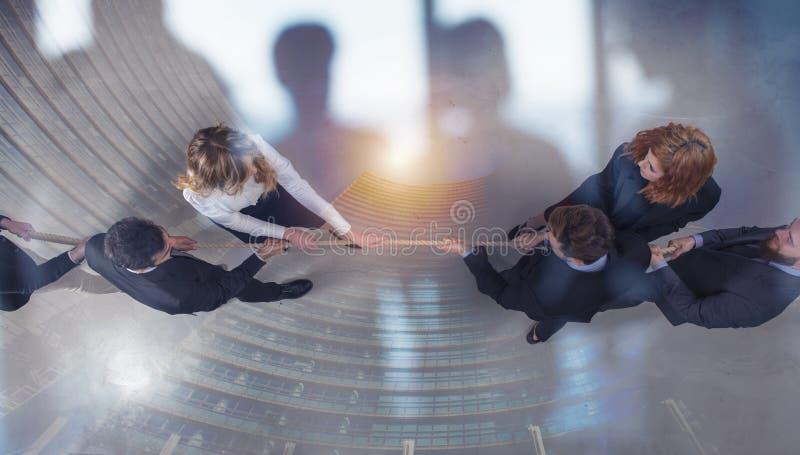 Den rivaliserande den affärsmannen och kvinnan konkurrerar för kommandot, genom att dra repet dubbel exponering royaltyfria foton