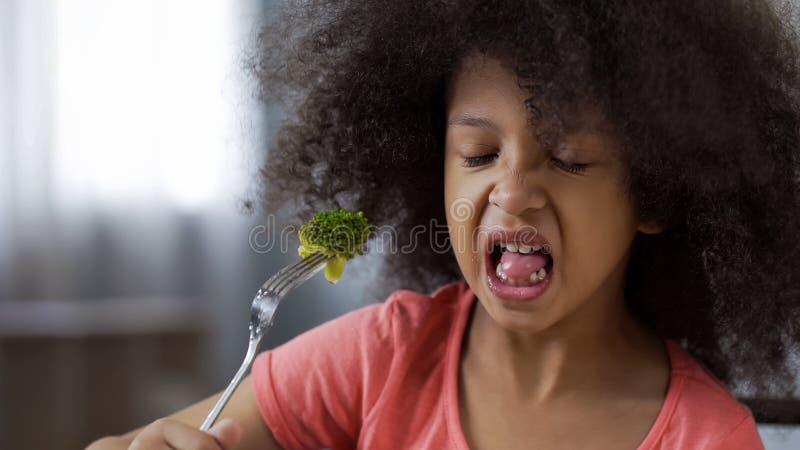 Den roliga afrikanska flickan som äter broccoli med enorm avsmak som är sund bantar för barn royaltyfri bild