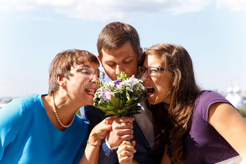 Den roliga brudgummen med modern och systern äter buketten av blommor arkivbilder