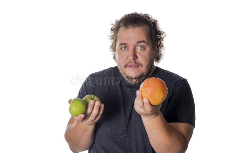 Den roliga feta mannen rymmer frukter på vit bakgrund Viktförlust och sunt äta arkivbilder