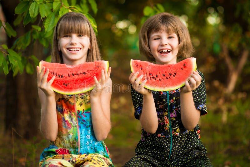 Den roliga flickan för små systrar äter vattenmelon i sommar royaltyfria foton