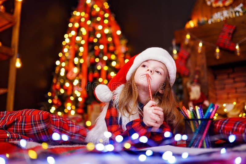 Den roliga flickan, i att drömma för jultomtenhatt, skrivar brevet till jultomten arkivfoto