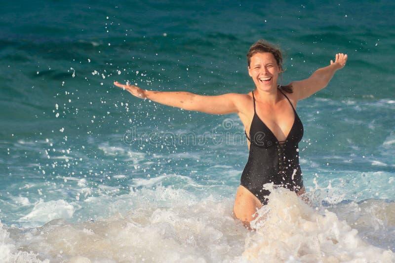 Den roliga flickan i baddräkt simmar i havsvatten Kvinna som plaskar i havsvågor och droppar arkivbilder