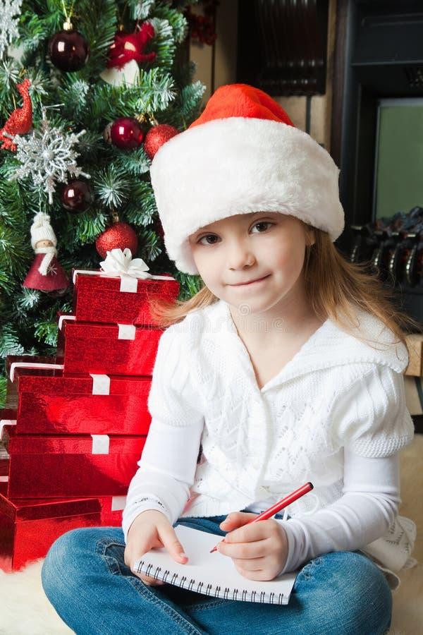 Den roliga flickan i den Santa hatten skriver bokstaven till Santa royaltyfri foto