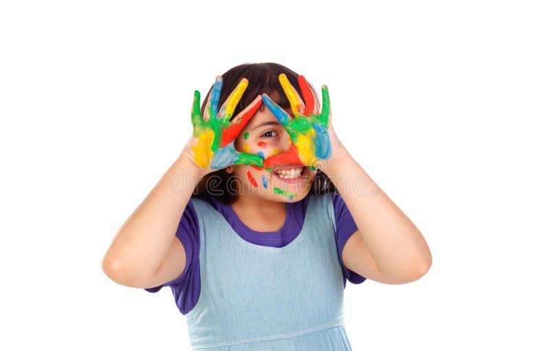 Den roliga flickan med hennes händer smutsar ner av målarfärg royaltyfri bild