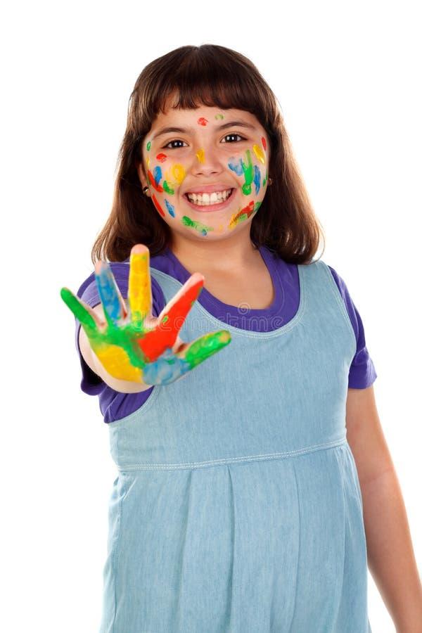 Den roliga flickan med hennes händer smutsar ner av målarfärg royaltyfri foto