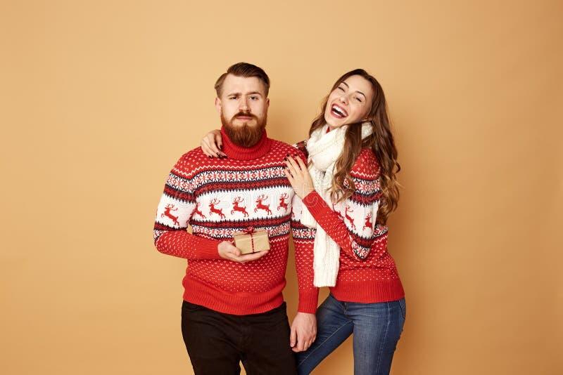 Den roliga flickan och röda för grabb iklädda och vita tröjor med hjortar står tillsammans på en beige bakgrund i studion arkivfoton