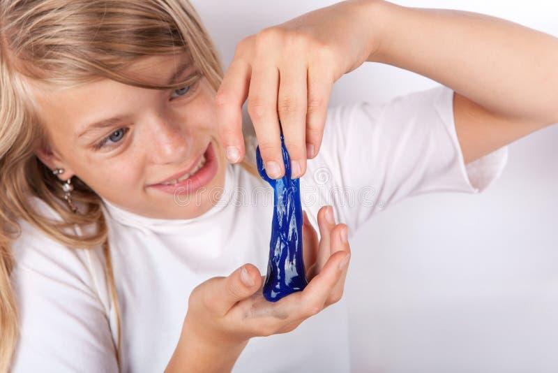 Den roliga flickan som spelar med blå slam, ser som smörja arkivfoto