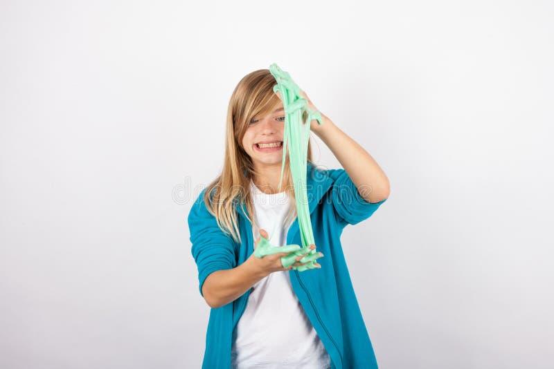 Den roliga flickan som spelar med grön slam, ser som smörja royaltyfri fotografi