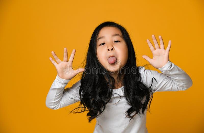 Den roliga gulliga lilla asiatiska flickan visar tungan fotografering för bildbyråer