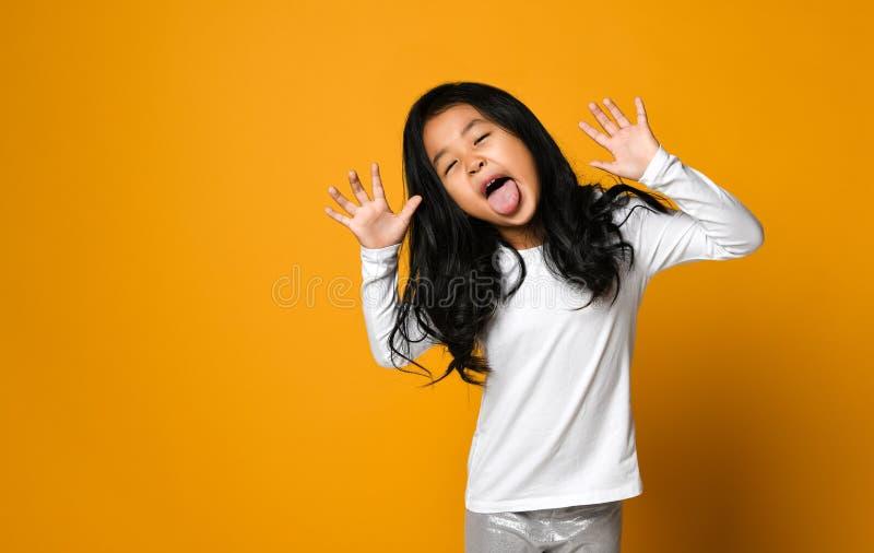 Den roliga gulliga lilla asiatiska flickan visar tungan royaltyfria bilder