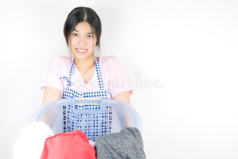 Den roliga hemmafrun bär en korg mycket av tvätterit royaltyfria bilder