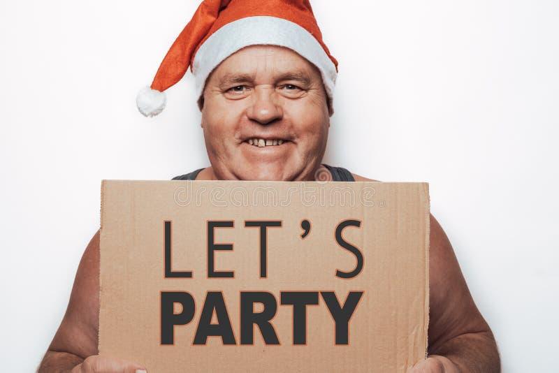 Den roliga le mogna mannen i rött Santa Claus hattinnehav i handpapp med inskriften - låt oss festa arkivfoto