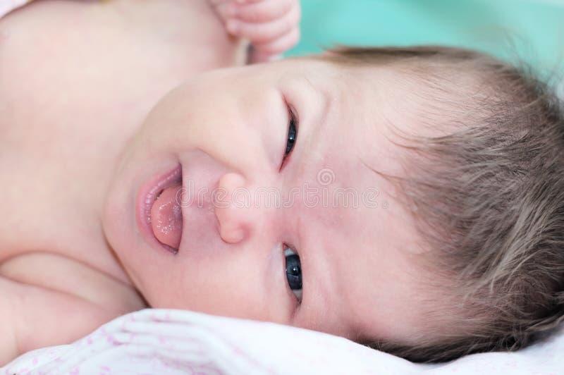 Den roliga le och rynka nyfödda ståenden behandla som ett barn i hennes första månadliv arkivbild