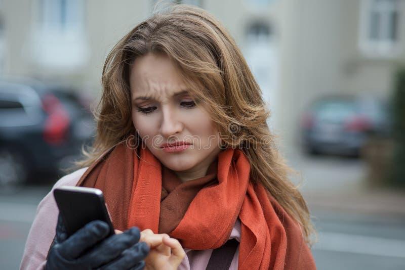 Den roliga ledsna kvinnan som ser tänka upp se dåliga nyhetersms, kommenterar royaltyfri bild