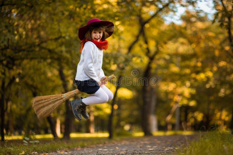 Den roliga lilla flickan flyger på kvasten i höst royaltyfri foto