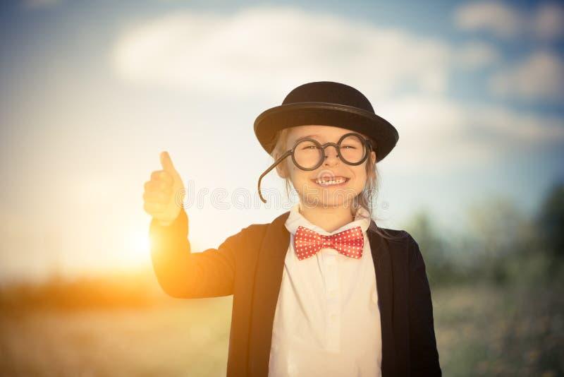 Den roliga lilla flickan i fluga- och plommonstopvisning tummar upp royaltyfria bilder
