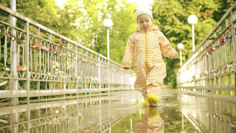 Den roliga lilla flickan i orange vattentäta regnrock- och gummiregnkängor går på pöl efter regn royaltyfria bilder