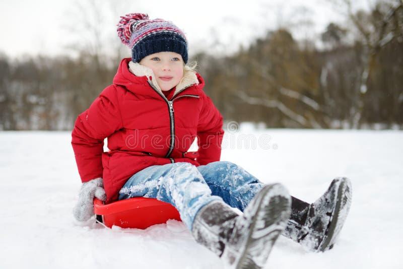 Den roliga lilla flickan som har gyckel med en släde i härlig vinter, parkerar Gulligt barn som spelar i en snö royaltyfria bilder