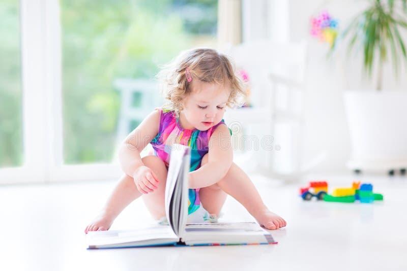 Den roliga lockiga litet barnflickan i rosa färger klär läseboken royaltyfria foton
