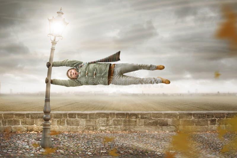 Den roliga mannen får blåst bort av en storm fotografering för bildbyråer