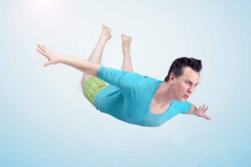 Den roliga mannen i kortslutningar flyger i himlen Begrepp av en turist som söker en semester arkivfoton