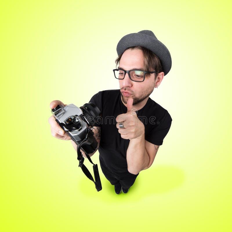 Den roliga mannen med hatten och photocameraselfieskratt ser som caric royaltyfri bild