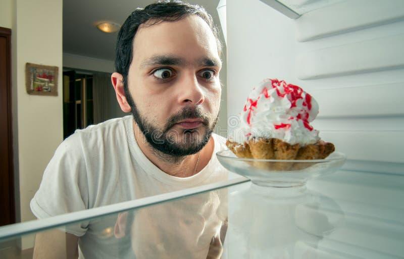 Den roliga mannen ser den söta kakan i kylen royaltyfri bild