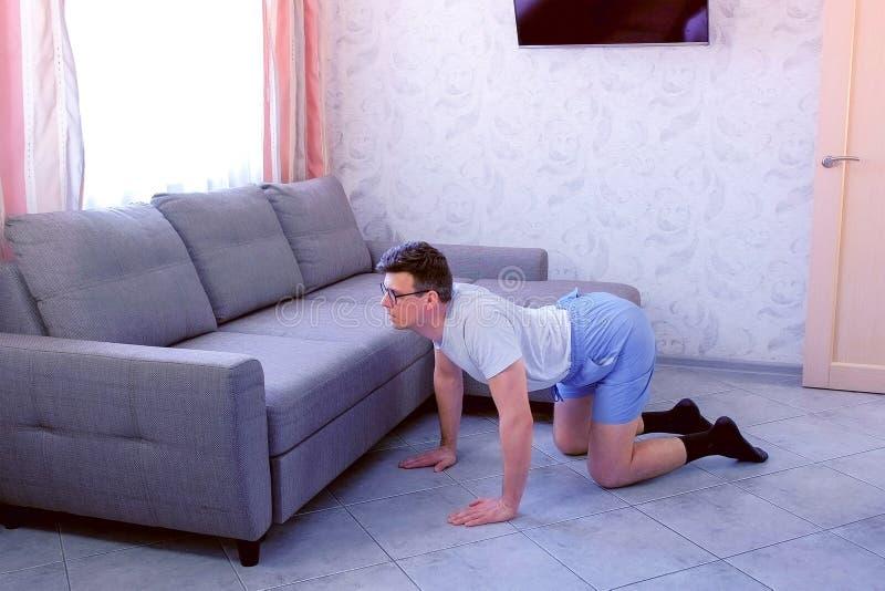 Den roliga nerdmannen gör sträcka övningen för tillbaka att stå på alla fours hemma Sporten blidkar begrepp royaltyfria bilder